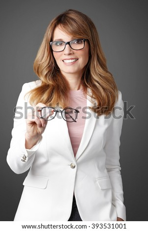 Portrait of middle age businesswoman wearing eyeglasses while standing at isolated background and holding in her hand glasses.