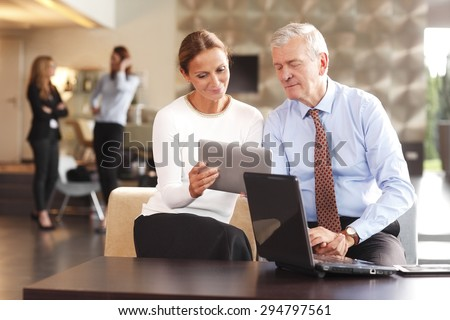 Portrait of middle age businesswoman with digital tablet sitting at conference and consulting with senior sales manager. Business people standing at background and discuss their idea.  - stock photo
