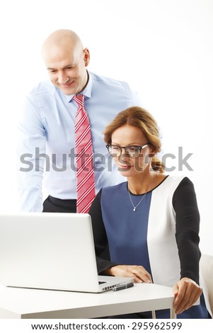 Portrait of middle age businesswoman working with laptop on presentation while businessman standing behind her. Teamwork at office.