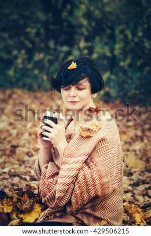 Portrait of middle age caucasian brunette woman with leaves in hair, yellow orange woolen scarf, sitting on ground outside in park drinking coffee with eyes closed, cozy autumn fall mood concept - stock photo