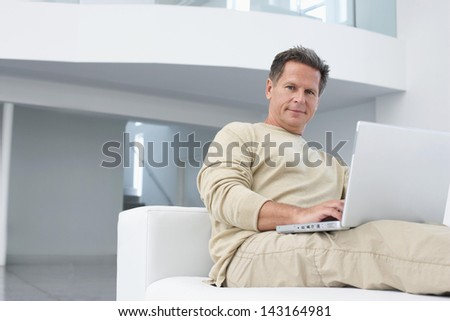 Portrait of middle age man using laptop on sofa in living room
