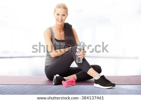 Portrait of middle age smiling woman sitting at gym while holding in her hand a bottle of water and relaxing after fitness workout.  - stock photo
