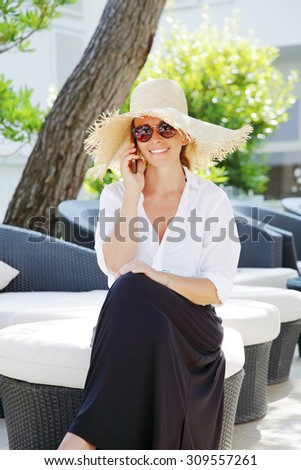 Portrait of middle age woman sitting at garden and making call while looking at camera.