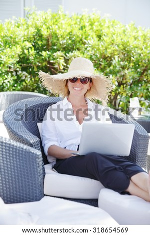 Portrait of middle age woman sitting outdoors with her laptop and working online during her summer vacation.  - stock photo