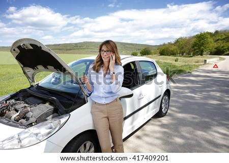 Portrait of middle age woman standing alongside her broken down car on the road and making call while waiting for emergency assistance.