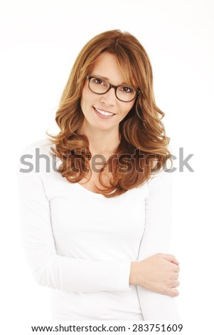 Portrait of middle age woman with arms crossed standing against white background.  - stock photo