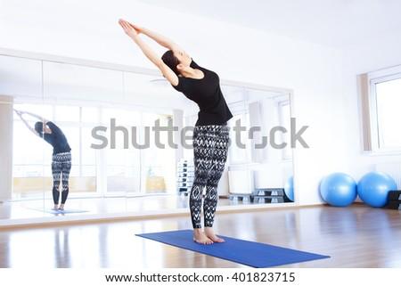 Portrait of middle age yoga instructor doing yoga at studio.  - stock photo