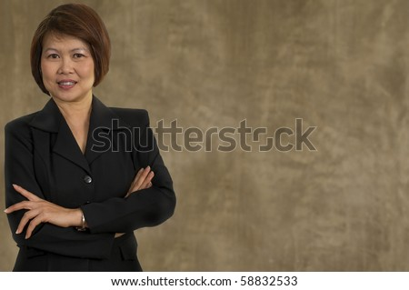 Portrait of middle aged Asian woman with her arms crossed - stock photo