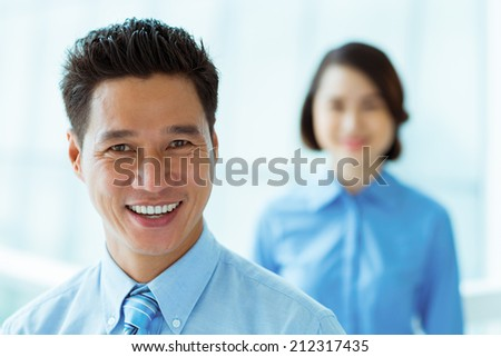 Portrait of middle-aged businessman and his female colleague in background - stock photo