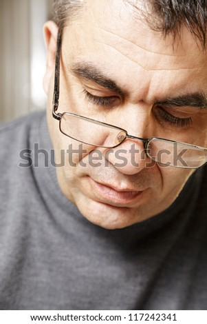 Portrait of middle-aged caucasian man in eyeglasses looking down front view - stock photo