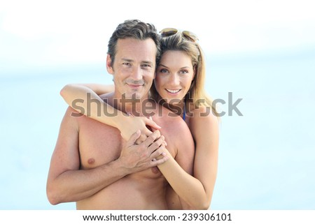 Portrait of middle-aged couple embracing by the beach - stock photo
