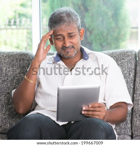 Portrait of middle aged Indian man headache while reading on digital tablet computer at home. - stock photo