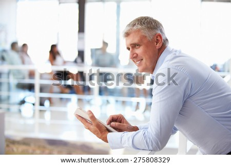 Portrait of middle aged man in office using tablet - stock photo