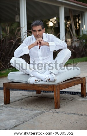 Portrait of middle aged man wearing white shirt and pant sitting with legs crossed - stock photo