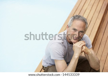 Portrait of middle aged man with hands on chin relaxing by pool - stock photo