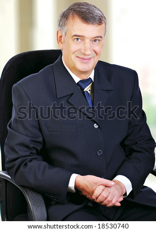 Portrait of middle aged senior business sat in chair smiling with hands folded on lap. - stock photo