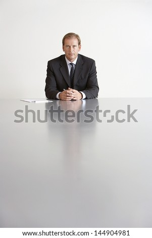 Portrait of middle aged serious businessman sitting at conference table - stock photo