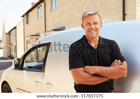 Portrait of middle aged tradesman standing by his van - stock photo