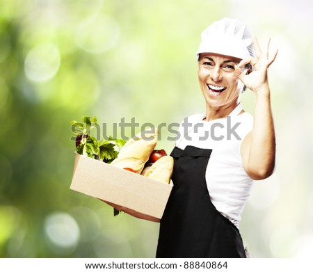 portrait of middle aged woman carrying food against a nature background - stock photo