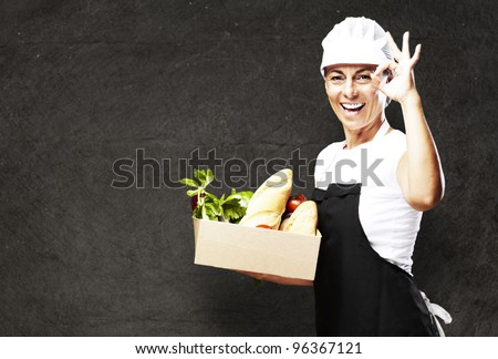 portrait of middle aged woman carrying food against a vintage wall - stock photo