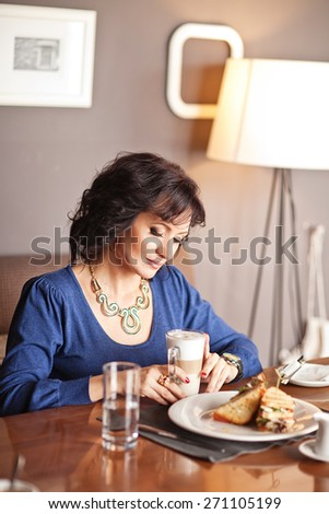 Portrait of middle-aged woman eating breakfast in cafe - stock photo