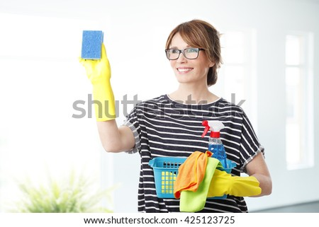 Portrait of middle aged woman holding a spray bottle and sponges in her hand while cleaning glass.