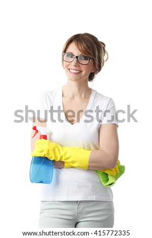 Portrait of middle aged woman holding in her hand a spray bottle and a microfiber cloth while standing at isolated background.