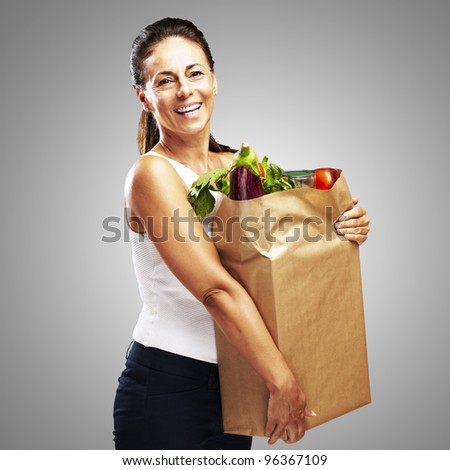 portrait of middle aged woman holding the purchase over grey background - stock photo