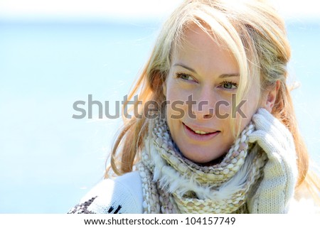 Portrait of middle-aged woman in winter at the beach - stock photo