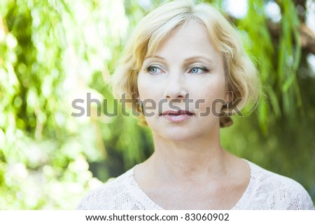 Portrait of middle aged woman on the nature background - stock photo