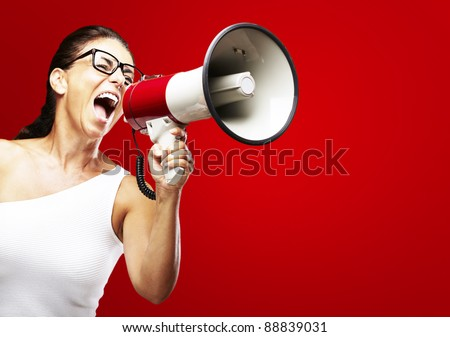 portrait of middle aged woman shouting using megaphone over red background - stock photo