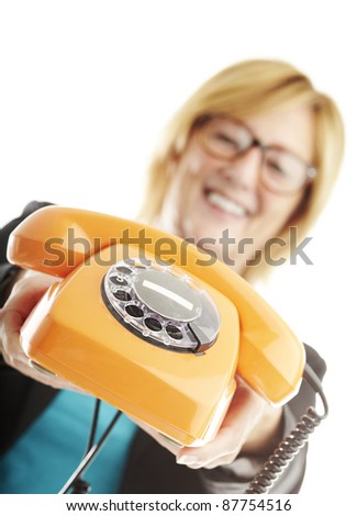 portrait of middle aged woman showing vintage telephone over white
