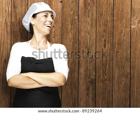 portrait of middle aged woman smiling against a wooden wall