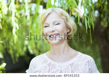 Portrait of middle aged woman smiling on the nature background - stock photo
