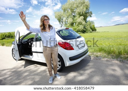 Portrait of middle aged woman standing alongside her broken down car and and waving with her hand for help.