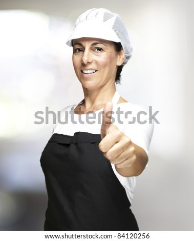 portrait of middle aged woman wearing apron and mesh top hat indoor - stock photo