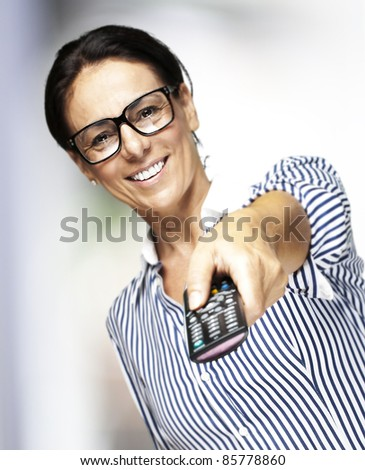 portrait of middle aged woman wearing glasses using a remote control tv indoor - stock photo