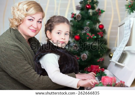 Portrait of middle aged woman with a litter girl posing near piano - stock photo