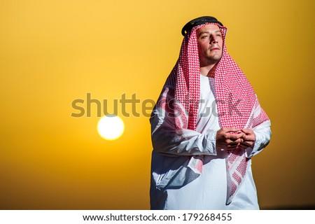 Portrait of Middle Eastern Arab man in desert on sunset time. - stock photo