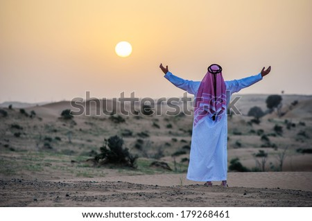 Portrait of Middle Eastern Arab man in desert on sunset time. - stock photo