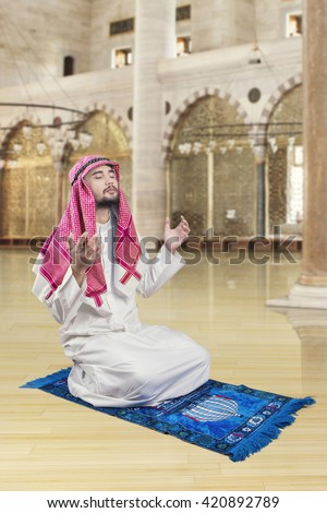 Portrait of middle eastern man sitting in the mosque while praying to the GOD - stock photo