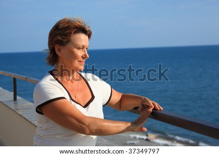 portrait of middleaged woman on balcony over sea