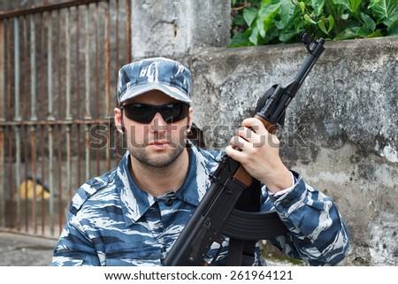 Portrait of military caucasian man with black sunglasses in urban warfare holding machine gun - stock photo