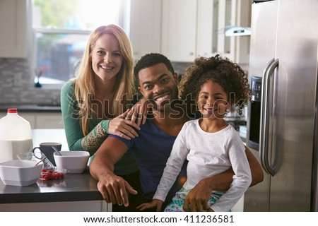 Portrait of mixed race couple and daughter in the kitchen - stock photo