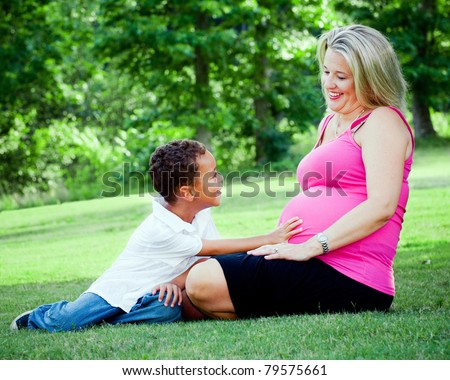 Portrait of mixed race mother and son outdoors with pregnant woman and mom