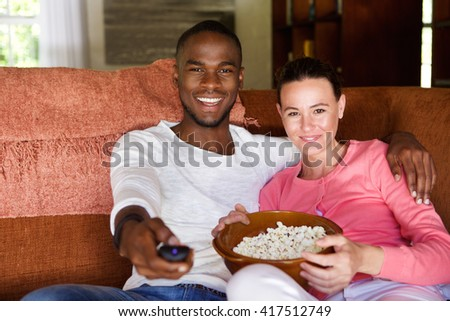 Portrait of mixed race young couple sitting on living room sofa watching a movie and eating popcorn  - stock photo