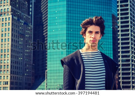 Portrait of Modern American College Student in New York, wearing fashionable long coat, striped undershirt, standing in front of busy business district with high buildings. Instagram filtered effect.  - stock photo