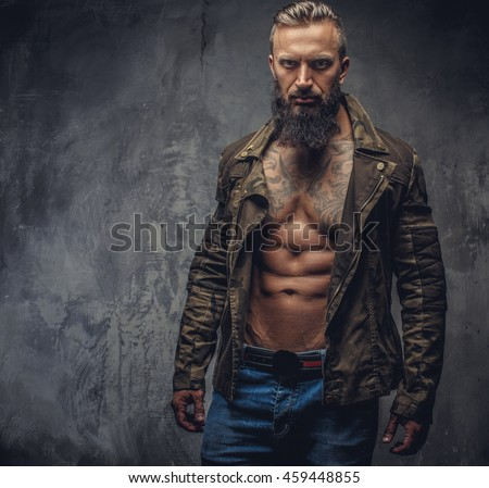 Portrait of modern bearded male in denim jeans and casual jacket dressed on naked torso.