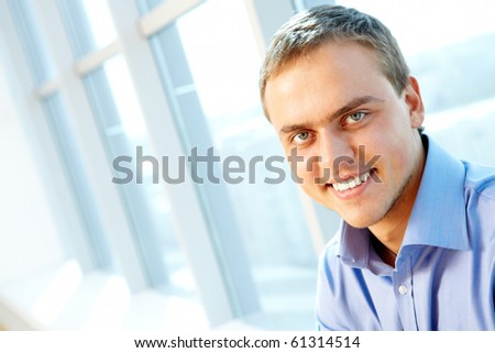 Portrait of modern businessman looking at camera with smile - stock photo