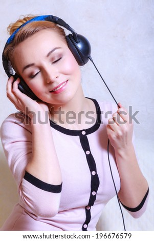 Portrait of modern businesswoman young woman or student girl with headphones listening to music mp3 relaxing or learning language. Indoor. - stock photo